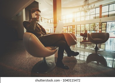 Young bearded man entrepreneur in formal suit is adjusting his glasses while sitting in the curvy armchair with the laptop in hotel reception area in classic style and waiting for his partner