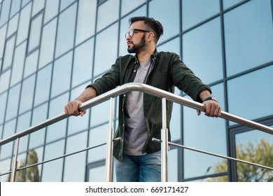 young bearded man in eyeglasses leaning on railing at office building
