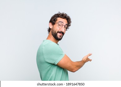 young bearded man feeling happy and cheerful, smiling and welcoming you, inviting you in with a friendly gesture