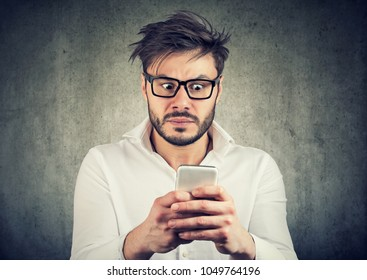 Young bearded man in glasses watching smarpthone and looking scared with bad news.