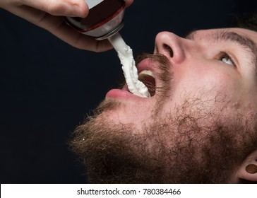 Young bearded man gorges on whipped cream from can