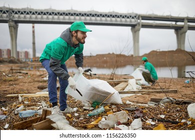 Young bearded man in green uniform collecting litter on coast