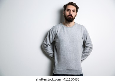 Young bearded man in grey shirt with long sleeves on light grey background. Mock up