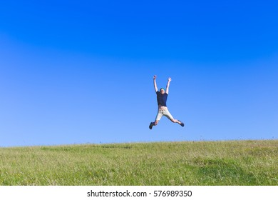 young bearded man happily jumping high on field with green grass and blue sky, view from long distance, success concept