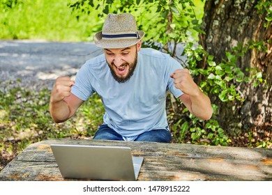 Young bearded man in a hat is sitting near a laptop in nature, emotionally rejoices looking at the screen.
