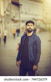 young bearded man, hipster, stands on the street of the city
