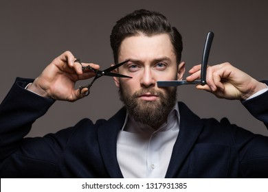 Young bearded man holding Barber scissors and razor near his face standing isolated on gray background