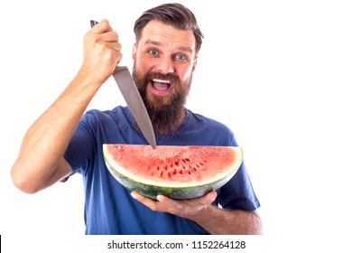 Young bearded man holding knife and green red watermelon with funny expresion on white
