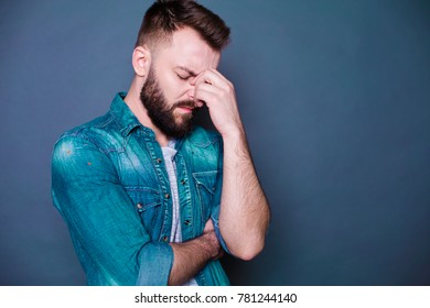 A young bearded man holds his head in pain against a gray background.