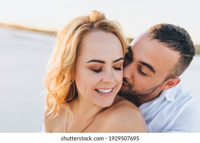 A young bearded man hugs a blonde against a background of white sand and gently kisses her neck. Portrait of emotional people at sunset. Love of newlyweds in the desert. Love story.