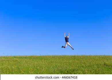 young bearded man jumping high on field with green grass and blue sky, view from long distance