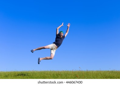 young bearded man jumping high on field with green grass and blue sky