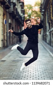 Young bearded man jumping in urban street wearing casual clothes. Happy guy with beard and modern hairstyle.