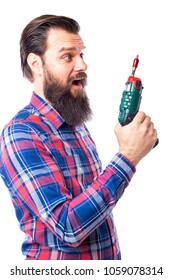 Young bearded man; looking at battery screwdriver in his hand; isolated on white