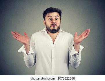Young bearded man looking super puzzled and shrugging shoulders in question holding hands apart.