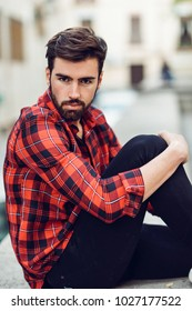 Young bearded man, model of fashion, wearing a plaid shirt with sitting in the street. Guy with beard and modern hairstyle in urban background.