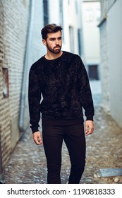 Young bearded man, model of fashion, walking in urban background wearing casual clothes. Guy with beard and modern hairstyle in the street.