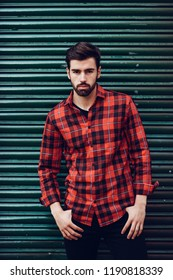 Young bearded man, model of fashion, wearing a plaid shirt with a green blind behind him. Guy with beard and modern hairstyle in urban background.