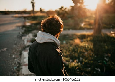Young bearded man on his back looking at sunset outdoors with urban casual clothes.