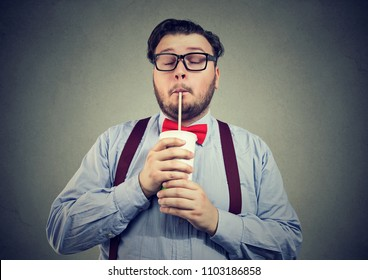 Young bearded man with overweight holding eyes closed and drinking sweet soda with deep enjoyment