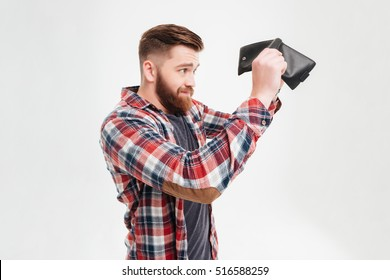 Young bearded man in plaid shirt looking inside his empty wallet to camera over white background over white background