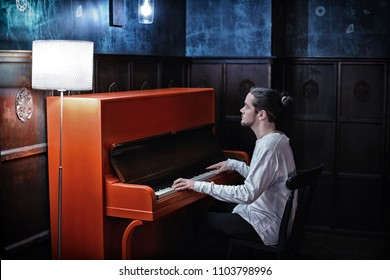 Young bearded man playing red piano