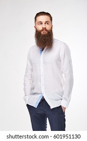 Young bearded man posing in studio in trendy linen white shirt and blue pants