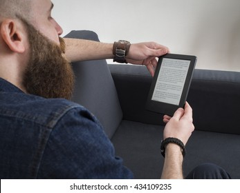 Young bearded man reading e book on the sofa. Shot from behind. Focus on the ebook.