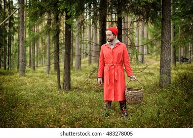 Young bearded man in red clothes standing alone in deep forest