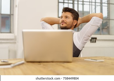 Young bearded man relaxing on chair while sitting in front of laptop at office