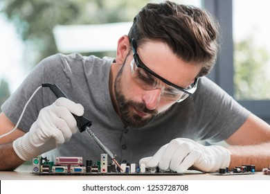 Young Bearded Man Repairing Motherboard from PC. Repair Shop. Worker with Tools. Computer Hardware. Magnifying Glass. Soldering Iron. Digital Device. Laptop on Desk. Electronic Devices Concept.