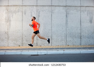 Young bearded man running on the street. Healthy lifestyle concept.