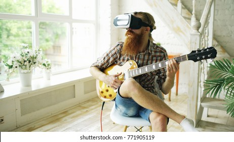 Young bearded man sitting on chair learning to play guitar using VR 360 headset and feels him guitarist at concert at home