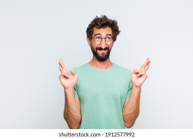 young bearded man smiling and anxiously crossing both fingers, feeling worried and wishing or hoping for good luck