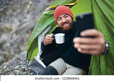 Young bearded man smiling, drinking tea and taking selfie in mountains from his smart phone. Traveler man with beard wearing red hat take self portrait vie mobile phone after hiking. Travel, lifestyle