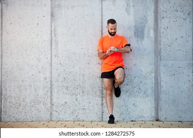 Young bearded man standing against the wall and setting stopwatch on his wrist. Healthy lifestyle concept.