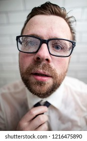 A young bearded man with a strange expression on his face, sweaty glasses covered with drops and wet clothes is standing in the bathroom after taking a shower in a shirt and tie. Close-up.