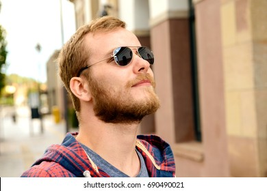 young bearded man with sunglasses in checkered shirt standing in front of city background