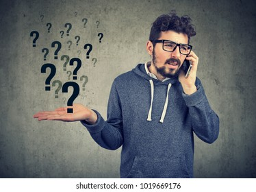 Young bearded man talking on smartphone in misunderstanding on gray background.