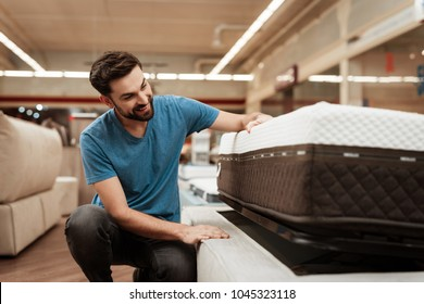 Young bearded man is testing mattress in furniture store. Orthopedic mattress for a healthy posture. Checking mattress in furniture store.