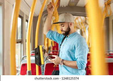 Young bearded man texting on smart phone in the bus.