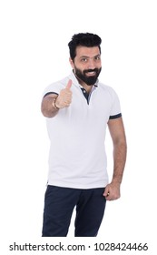 A young bearded man thumbs up and smile, in a casual outfit, isolated on a white background.