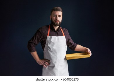 Young bearded man, waiter, chef, dressed in white apron with picture of tomatoes,standing,holding in one hand blank wooden tray and looking at camera.