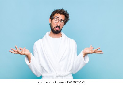 young bearded man wearing a bath robe shrugging with a dumb, crazy, confused, puzzled expression, feeling annoyed and clueless