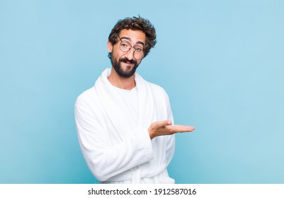 young bearded man wearing a bath robe smiling cheerfully, feeling happy and showing a concept in copy space with palm of hand