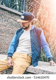 Young Bearded Man wearing in Blue Cap with label Mockup and blank gray t-shirt, blue baseball jacket, sitting on the stone railings in city park