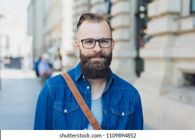 Young bearded man wearing glasses and a denim top standing in an urban street looking thoughtfully at the camera with a quiet smile