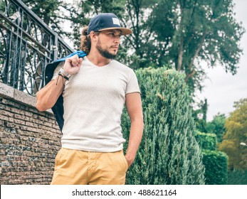 Young Bearded Man wearing gray t-shirt and Blue Baseball Cap mockup holding a jacket in hand