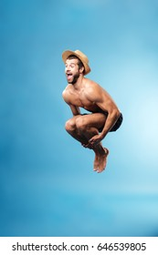 Young bearded man wearing hat jumping high isolated over blue
