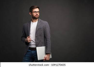Young bearded man wearing jacket and glasses holding laptop and looking away with confidence.